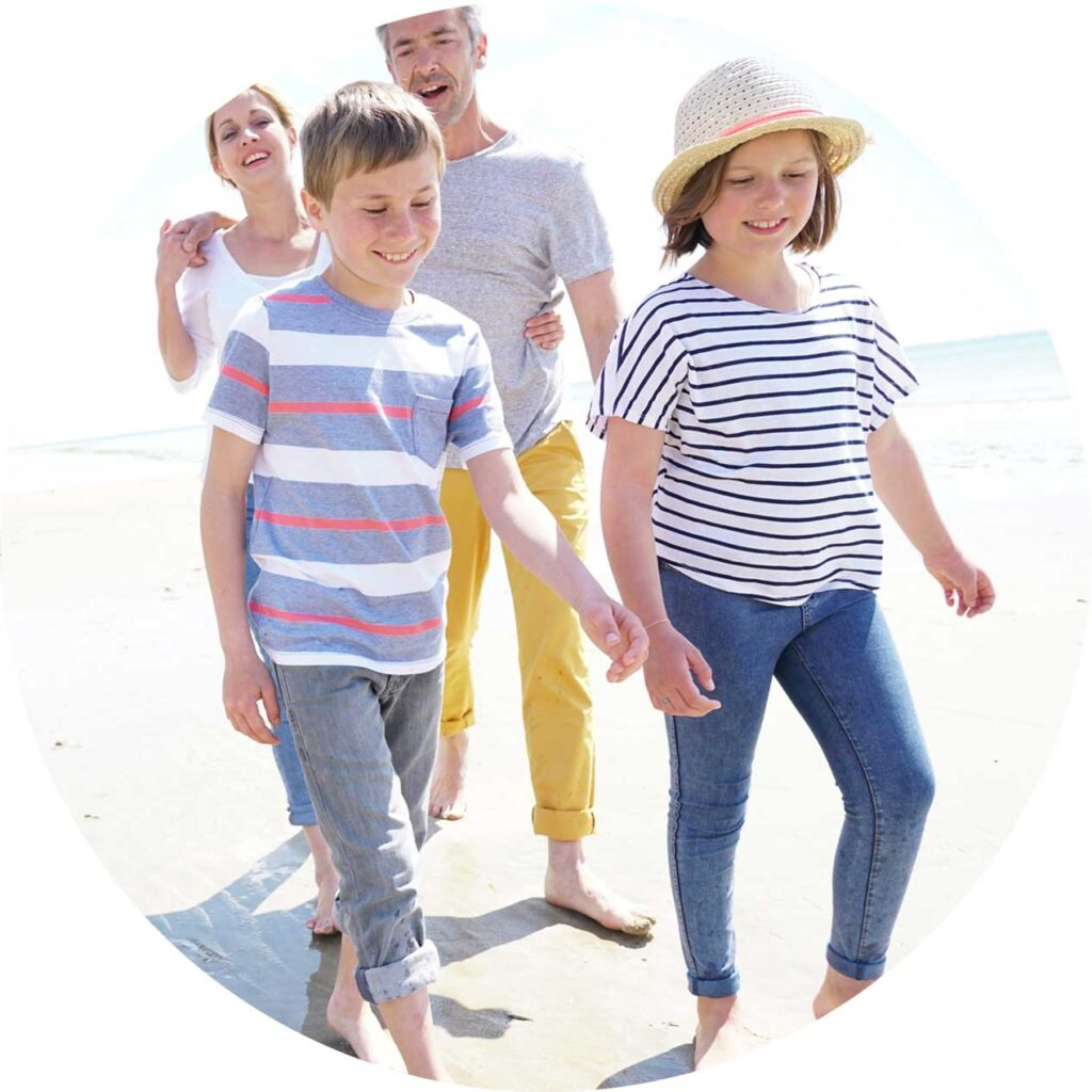 happy children walking on the beach with parents